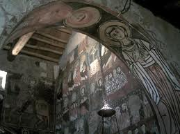 """The Monastery of St. Moses existed from the middle of the sixth century, and belonged to the Syrian Antiochian Rite. The present monastery church was built in the Islamic year 450 (1058 AD), according to Arabic inscriptions on the walls, which begin with the words: """"In the name of God the Merciful, the Compassionate"""". The frescoes go back to the 11th and 12th centuries. In 1984, restoration work began through a common initiative of the Syrian State, the local Church, and a group of Arab and European volunteers. The restoration of the monastery building was completed in 1994 thanks to cooperation between the Italian and Syrian States."""